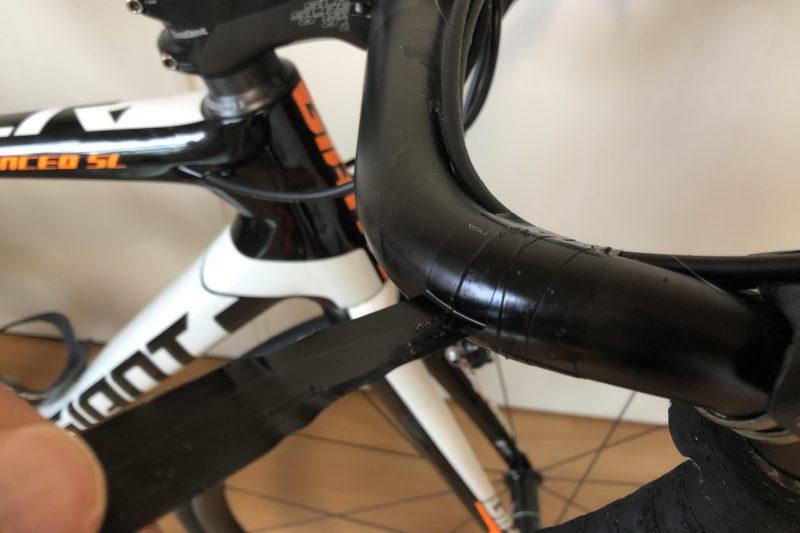 ロードバイクのハンドルでビニールテープを剥がしているところ